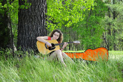 Teenage Girl Playing Guitar In Woods. Girl playing a guitar in the woods. Peaceful and serene Royalty Free Stock Images