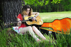 Teenage Girl Playing Guitar In Woods. Girl playing a guitar in the woods. Peaceful and serene Royalty Free Stock Photography