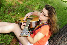 Teenage Girl Playing Guitar In Woods. Girl playing a guitar in the woods. Peaceful and serene Royalty Free Stock Photos