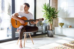 Playing the guitar. Young beatiful man with guitar in hands sitting on chair and looking away Royalty Free Stock Image