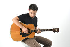 Playing Guitar. Young man playing acoustic guitar Royalty Free Stock Photos