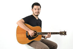 Playing Guitar. Young man playing acoustic guitar Royalty Free Stock Images