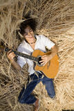 Playing guitar02. Cool guy laying in a cornfield playing guitar royalty free stock image