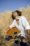 Playing guitar04. Cool guy laying in a cornfield playing guitar stock photo