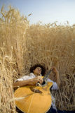 Playing guitar05. Cool guy laying in a cornfield playing guitar stock photography