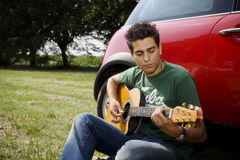 Playing guitar10. Cool guy playing guitar besides his car stock photography