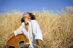 Playing guitar11. Cool guy laying in a cornfield playing guitar royalty free stock photography