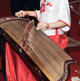 Playing guzheng. A woman in traditional costume playing guzheng.Guzheng is an traditional Chinese musical instrument,It belongs to the zither family of string Royalty Free Stock Images