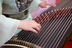 Playing Guzheng. A girl is playing Guzheng.The guzheng or gu zheng (Chinese: 古箏), also simply called zheng (箏, gu 古 means ancient), is a Chinese plucked Stock Photography