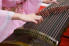 Playing Guzheng. A girl is playing Guzheng.The guzheng or gu zheng (Chinese: 古箏), also simply called zheng (箏, gu 古 means ancient), is a Chinese plucked Royalty Free Stock Photo