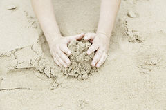 Playing with hands in the sand Royalty Free Stock Photo