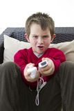 Playing Hard. A white male caucasian 6 years old kid playing video game on the cauch Stock Image