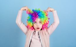 Playing with her hair. Funny kid with curly synthetic hair. Cute little girl with fancy hair. Adorable small child. Wearing bright clown hair wig royalty free stock photos