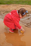 Playing with her water toys on muddly puddles Royalty Free Stock Photo