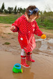 Playing with her water toys on muddly puddles Royalty Free Stock Photography