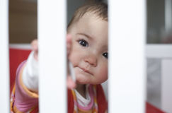 Playing hide-and-go-seek behind the bars white cot Stock Image