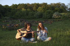 Playing it the hippie way!. Man and girl having fun outdoor, the men playing an acoustic guitar and the girl wearing a shirt with the peace sign stock image