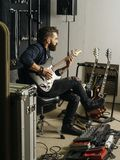 Playing his electric guitar in the recording studio. Photo of a man with beard sitting and playing his electric guitar in a recording studio stock photo