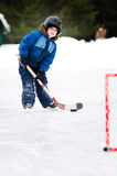 Playing hockey. Five year old boy playing ice hockey on an outdoor rink Stock Photos
