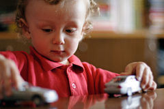 Playing in home (2). In an apartment a boy in a red shirt plays with the models of cars Stock Photography