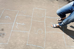 Playing in hopscotch outdoors Stock Image