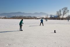 Playing ice hockey on a frozen lake. Austria, Europe. Royalty Free Stock Photo
