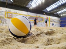 Playing indoor beach volleyball. Closeup of ball in sands royalty free stock images