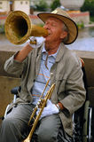 Playing Jazz on the Charles Bridge. Famous in Prague stiff-limbed street musician plays jazz on the Charles bridge in the capital of Czechia Prague while sitting Stock Photo