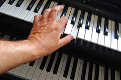 Playing keyboards. A hand poised above keyboards in a playing position Royalty Free Stock Photo