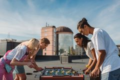 Playing kicker. Group of happy friends playing table football on roof Stock Photo