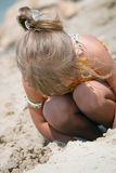 Playing kid girl on the beach. Kid girl playing with sand on the beach royalty free stock image