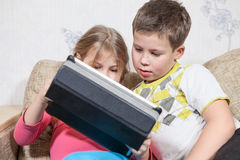 Playing kids sitting on sofa together, holding tablet pc with interesting game Stock Image