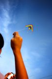Playing with Kite. People playing Kite over the blue sky (focus on kite Royalty Free Stock Photo