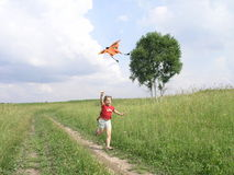 Playing with kite. Running child with kite in a meadow Stock Image