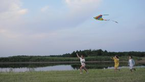 Playing with kite, active children running around the meadow have fun with toy in background of lake and trees