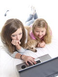 Playing with a laptop. Two girls and a dog is playing with a laptop Stock Photo
