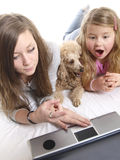 Playing with a laptop. Two girls and a dog is playing with a laptop Stock Images