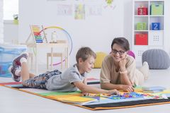 Playing and learning together. Little boy and smiling female therapist lying on the floor playing and learning together with alphabet letters stock photo