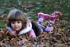 Playing with leaves. Little girl laying on the ground and playing with autumn leaves Royalty Free Stock Image