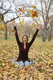 Playing in the Leaves. Girl playing in the leaves and throwing them in the air Royalty Free Stock Image