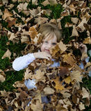 Playing in the leaves. Four year old child playing in the autumn leaves Stock Image