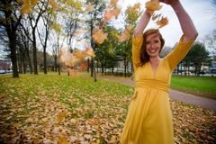 Playing with Leaves. A 24 year old caucasian woman plays with fallen leaves on a windy autumn day in a Providence, Rhode Island, USA park royalty free stock photography