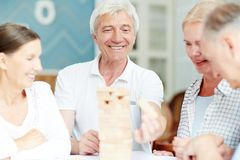 Playing at leisure. Group of mature friends playing board game during gathering at leisure Stock Images