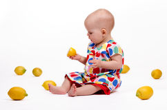 Playing with Lemons. Cute baby girl sitting on the floor playing with lemons Royalty Free Stock Photo