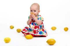 Playing with Lemons. Cute baby girl sitting on the floor playing with lemons Stock Photo