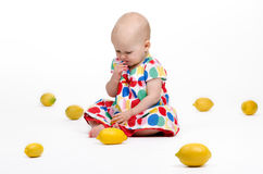 Playing with Lemons. Cute baby girl sitting on the floor playing with lemons Royalty Free Stock Images