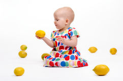 Playing with Lemons. Cute baby girl sitting on the floor playing with lemons Stock Photography