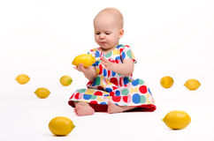 Playing with Lemons. Cute baby girl sitting on the floor playing with lemons Royalty Free Stock Photography