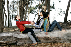 Playing on log. Three young friends, a guy and two girls sitting playfully on a log in the woods Royalty Free Stock Photo