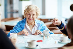 Playing lotto with senior friends. Cheerful elegant-looking elderly woman gathered with her friends in lovely coffeehouse and playing lotto enthusiastically Royalty Free Stock Photos